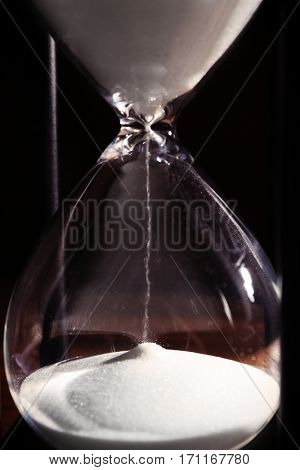 Time passing concept. Black hourglass with white sand, close up