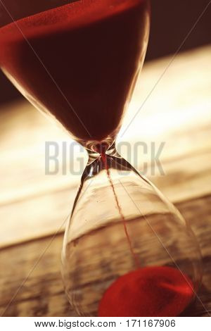 Time passing concept. Crystal hourglass with red sand on wooden background