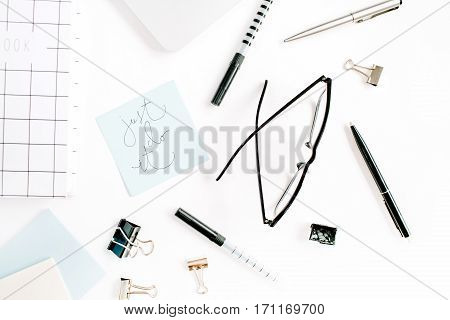White office desk frame with quote Just Do It and supplies. Laptop notebook pen clips glasses and office supplies on white background. Flat lay top view mockup.
