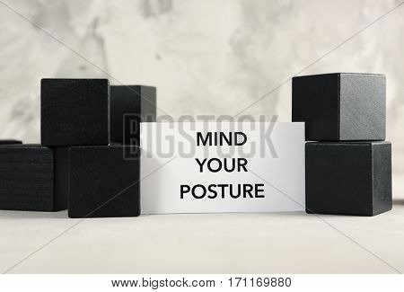 Paper with phrase MIND YOUR POSTURE an black cubes on gray background