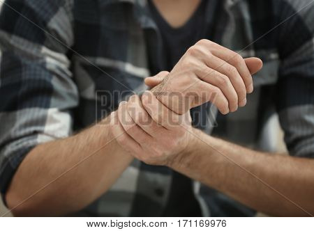 Man suffering from pain in wrist, closeup
