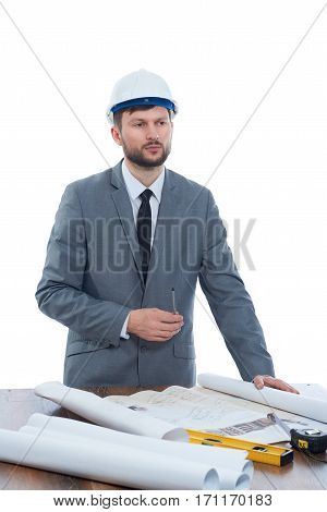 Professional builder with beard reading architecture plan of building and analyzing. Architect in gray suite and white safety hat looking away, standing at work place. Studio isolate.