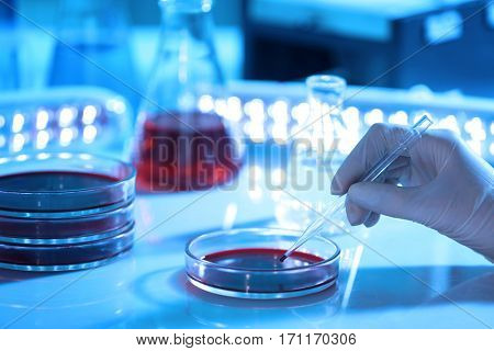 Scientist hand holding pipette with blood in laboratory