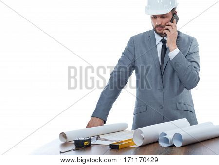 Young engineer talking on call phone at work place with table and many tools. Confident architect in gray suite and white safety hat reading architecture plan of building.