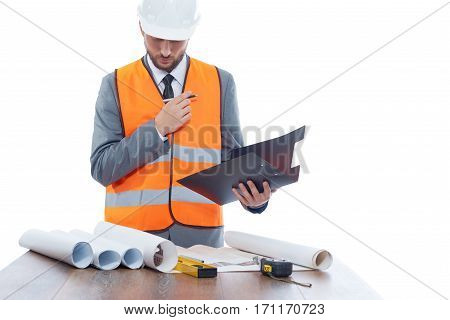 Engineer reading big drawing plan of building and analyzing. Architect with beard  wearing in orange vest, suite and white safety hat. Work place of builder.