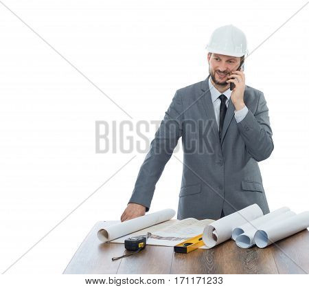 Engineer in gray suite and white safety hat talking on call phone and smiling. Confident architect reading architecture plan of building, standing at work place, near on table different tools.