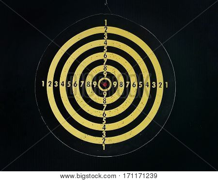 Close up picture of dart board on dark background.