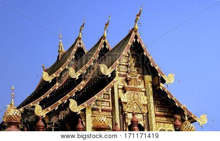 Details of northern style Thai temple roof on clear blue sky