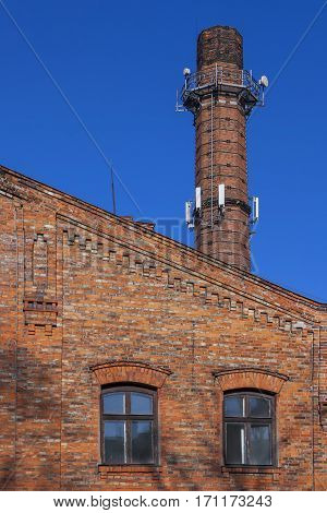 Cellular antenna on the tube of the old factory