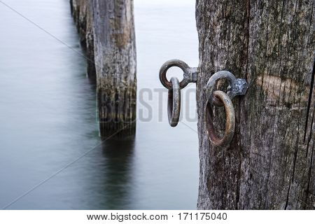 Weathered mooring poles of wood in the sea detail with metal eyelets long exposure selected focus
