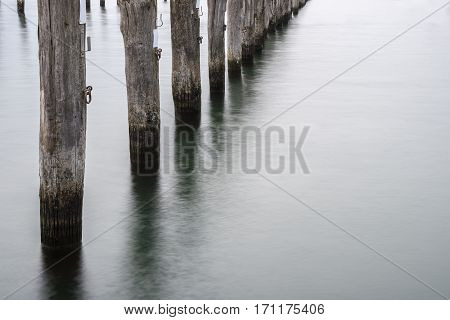 mooring poles of wood in the sea long exposure with copy space selected focus