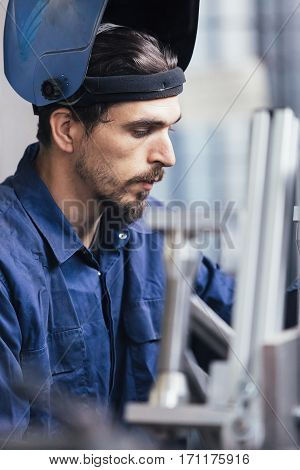 Young bearded man in mask looking doen at iron details