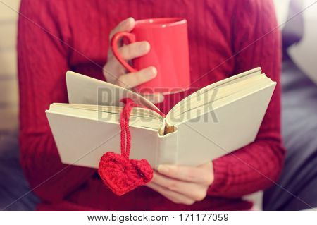 open book with a bookmark as a heart and a red mug in the hands / reading favorite stories