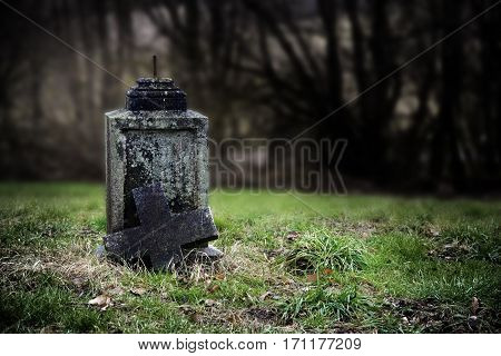 Broken stone cross weathered gravestone on an old abandoned cemetery concept for transience or gloomy halloween background with copy space