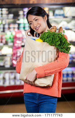 Woman talking on mobile phone while holding groceries in paper bag