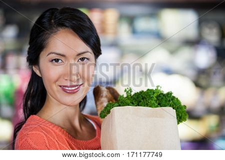 Portrait of woman holding groceries in grocery bag of supermarket