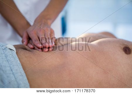 Physiotherapist giving stomach massage to a man in clinic