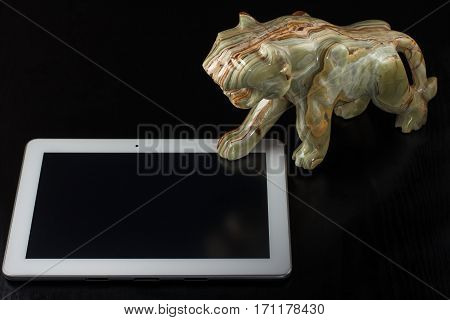 Onyx stone figure of a tiger and the tablet computer on a black background
