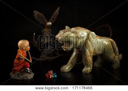 Little toy boy figure practicing martial arts in front of onyx stone figure of a tiger. Eagle figure on a background.
