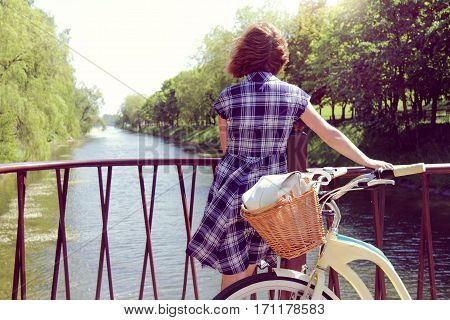 amateur travel on the bike rests on a bridge on the background of natural landscape / health-promoting pastime