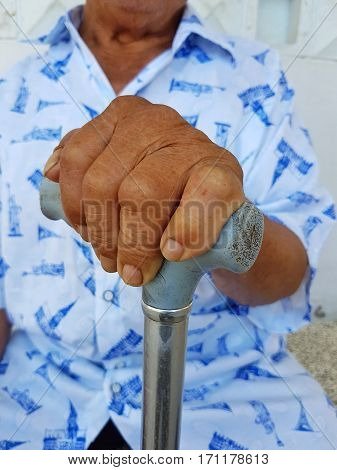 closeup hand of old asian male with a watch holding a cane