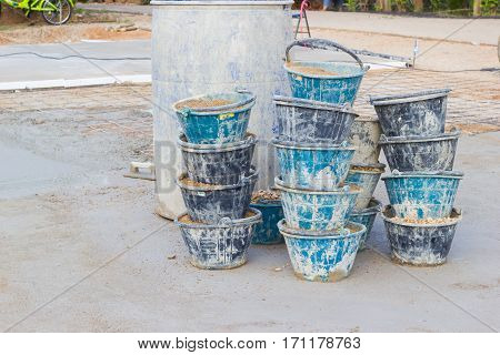 sand in many buckets prepared for mixing cement or concrete in construction site horizontal photo.