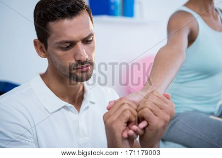 Physiotherapist giving hand massage to a woman in clinic