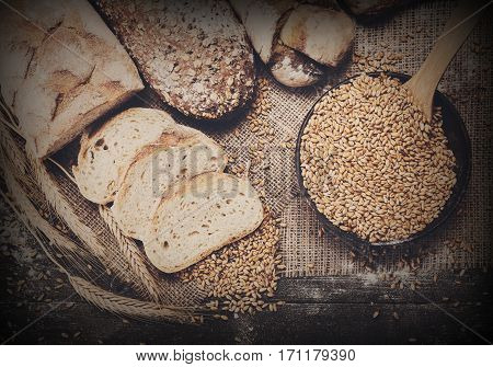 Plenty of sliced bread background. Bakery and grocery concept. Fresh, healthy whole grain sliced sorts of rye and white loaves, sprinkled flour on sacking and rustic wood table, food top view.