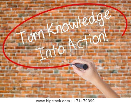 Woman Hand Writing Turn Knowledge Into Action! With Black Marker On Visual Screen