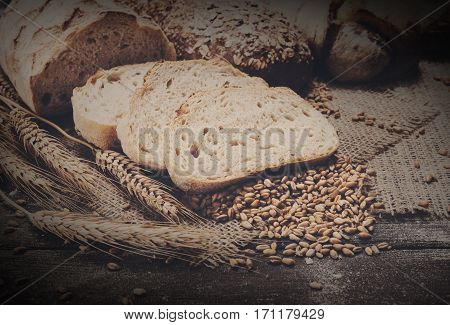 Plenty of sliced bread background. Bakery and grocery concept. Fresh, healthy sorts of rye and white loaves, sprinkled flour on sacking and rustic wood table, food closeup.