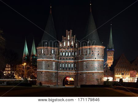 Holstentor and church towers in Luebeck iluminated at night the medieval city gate is a popular tourist attraction of the historic old town in Schleswig-Holstein Germany