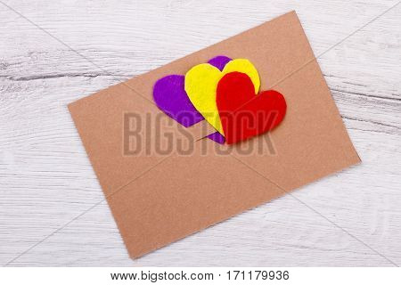 Hearts and card on wood. Colorful cut-out hearts. Creative and bright. Combination of paper and fabric.