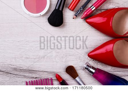 Make-up items and footwear. Cosmetic products on wooden surface. Shine like a star. Beauty is art.