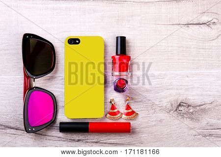 Sunglasses and phone near cosmetics. Make-up and accessories. Create your style. Beauty is in the details.