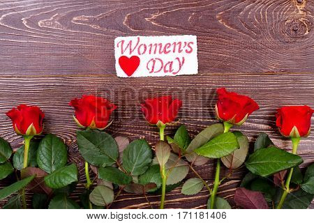 Women's Day card above roses. Heart and red wet flowers. Surprise your wife. Simple way of giving present.