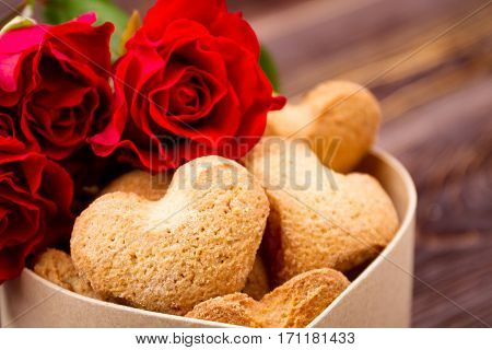 Box of cookies near roses. Flowers and heart-shaped shortbread. Art of baking biscuits. Tasty surprise for beloved.