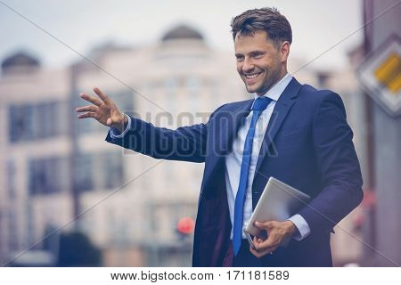 Handsome businessman hailing taxi on road
