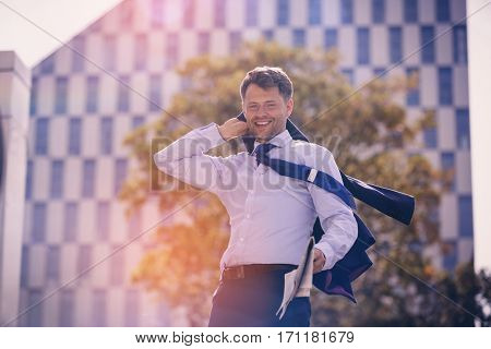 Portrait of businessman holding blazer and newspaper