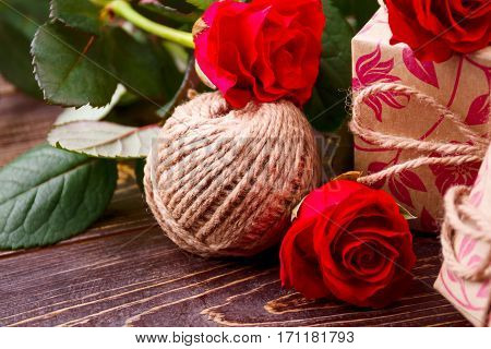 Ball of yarn and roses. Present box near flowers. Complete gift by festive mood. How to decorate a present.