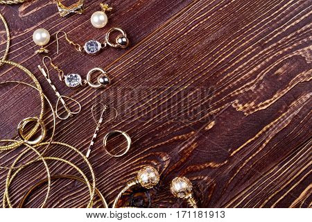 Jewelry on wooden surface. Bracelets, rings and earrings. Express your feelings. Memorable present for woman