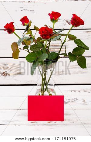 Red blank paper and roses. Card near vase with flowers. Greeting in old-fashioned way. Aesthetic present for woman.