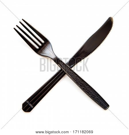 Black plastic crossed fork and knife isolated. Disposable cheap cutlery cross prohibition concept