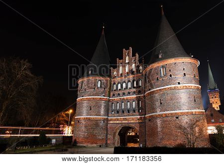 Holstentor in Luebeck at night medieval city gate a popular tourist attraction of the historic old town in Schleswig-Holstein Germany