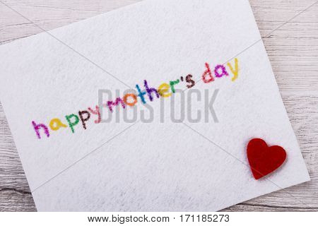 Happy Mother's Day greeting card. Fabric heart near inscription. Make colorful congratulation. Prepare a nice surprise.