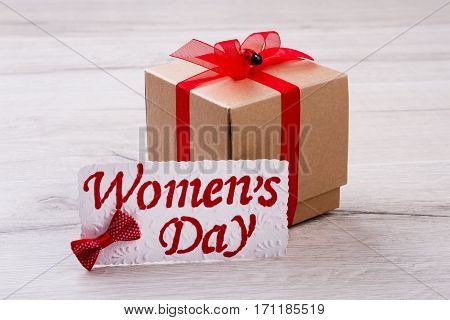 Women's Day gift. Greeting card, bow tie, present. Use ribbon to decorate package. Prepare gift for holiday.