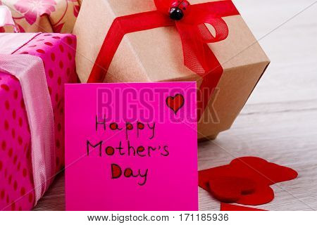 Gifts near Mother's Day card. Present with ribbon and hearts. Best gift is appreciation. Respect your mom.