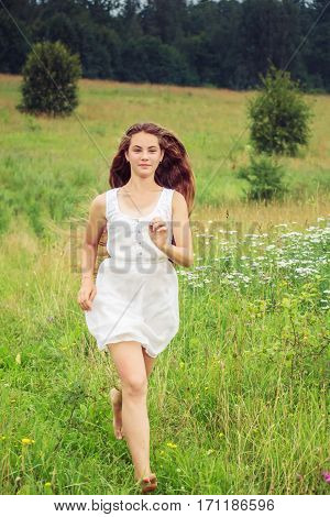 Beautiful girl with long hair running in a field.