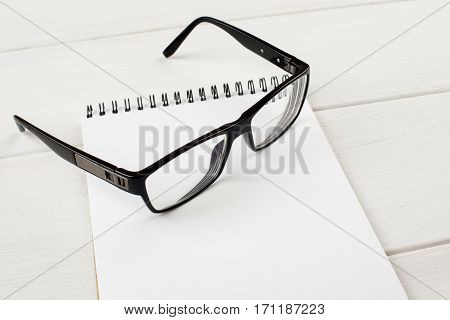 Open Notepad With Black-rimmed Eyeglasses On A Wooden Table