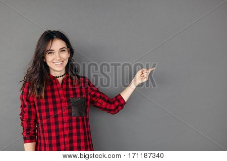 Smiling attractive young woman pointing away over grey background. Casual hipster girl in red checked shirt showing blank space with finger