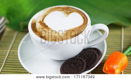 Hearts Cappuccino coffee and chocolate cookies. A cup of latte, cappuccino or espresso coffee with milk put on a wood table with dark roasting coffee beans. Drawing the foam milk on top.